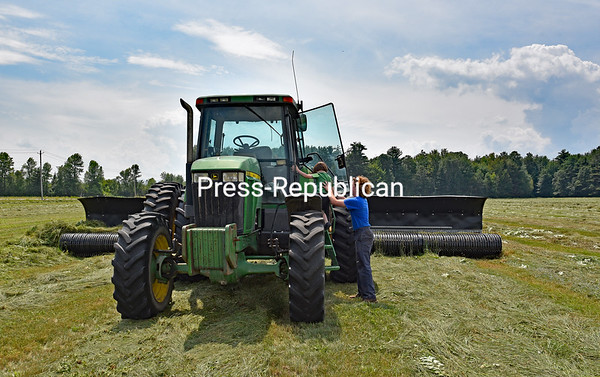 A fifth generation of farmers is born as Josh Remillard lifts his 5-year-old son, Wyatt, onto the hay merger while working a field on Route 22 in Peru. The Remillard farm uses a hay merger to make larger rows in getting ready for the chopper. It's been a wet summer in the North Country, so farmers are taking advantage of any sunshine they get in trying to harvest their hay.<br /> JOANNE KENNEDY/ P-R PHOTO