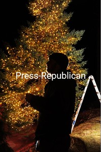 A silhouetted Nick McGrath checks out his tree-lighting work at the Mirror Lake Inn in Lake Placid. The popular vacation spot uses 300,000 lights to decorate for the holiday season. USAToday recently ranked the resort No. 2 in the United States in its Best Ski Hotel category. JACK LADUKE/ P-R PHOTO
