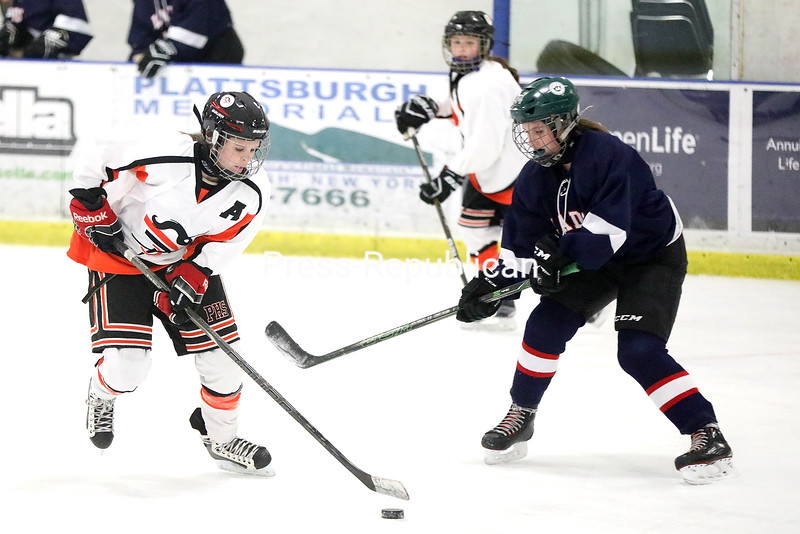 Plattsburgh High's Taylor Hackett (left) carries the puck past Franklin Academy's Vail St. Hilaire (right) during a Section VII girls hockey game Tuesday at Ameri-Can North Sports Center.<br /> KAYLA BREEN/ STAFF PHOTO