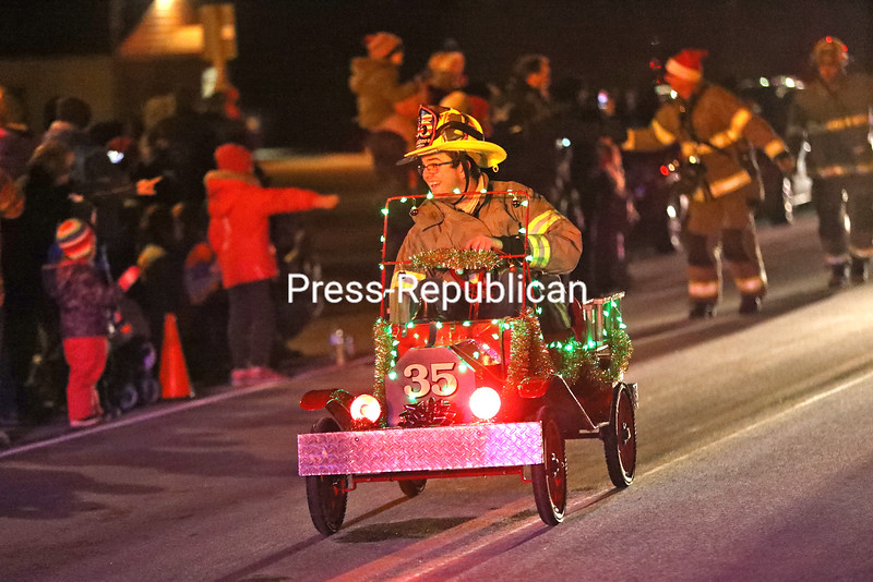 Town of Plattsburgh District 3 firefighter Josh Burnell leads his department in an illuminated miniature firetruck on Route 3 in Cadyville during the recent Decorated Firetruck Parade, a new event included with the Cadyville Community Tree Lighting. Ten departments and 14 holiday-inspired trucks participated in the parade. Plattsburgh Town Supervisor Michael Cashman, along with Assemblyman Billy Jones and Plattsburgh Deputy Town Supervisor Meg LeFevre, judged the entries and awarded the first Spirit of the Season award to District 3 for its creative firetruck decorations.<br /> KAYLA BREEN/ STAFF PHOTO