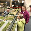 Dugan Smith, 6, peeks over the side of a train board, alongside his sister, 11-year-old Quincey Smith, while Adirondack and Lake Champlain Railroad member Bill Rooke works on an HO-scale train. The kids, who are from Elizabethtown, are among many people who have stopped in to check out the holiday-season train setup in a storefront near the former Gander Mountain at Champlain Centre mall in Plattsburgh. The display will be there through Dec. 17.<br /> LOIS CLERMONT/ STAFF PHOTO