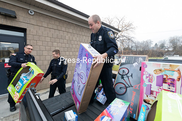 With the help of fellow City of Plattsburgh Patrolmen Carmen Rotella (from left) and Connor Kowalowski, TJ Rabideau loads gifts for delivery to the Clinton County Christmas Bureau. The gifts are just a few of those bought by Rabideau and his wife, Shannon, with close to $2,000 raised through donations of redeemable bottles and cans in the last month at the Police Department. Rabideau figured it would be a great way to give back to the community and plans to collect bottles into the new year for Christmas 2018. Those who wish to donate can drop off returnables at the police station on Pine Street. For information about the Christmas Bureau, including how to donate and for low-income families who wish to receive assistance, visit clintoncountychristmasbureau.org or call 518-562-1253. The deadline is Dec. 11 for those who live outside the city and Dec. 15 for those inside city limits. GABE DICKENS/ P-R PHOTO