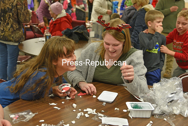 Tanya Roark, 11, gets into the holiday spirit as volunteer Katherine Campbell helps her create a Santa ornament at the 26th-annual Christmas Tree Lighting Ceremony in Peru. Outgoing Town Supervisor Peter Glushko and his wife, Karen, did the honors of lighting the Christmas tree at the town Gazebo, which was followed by refreshments, crafts and a visit with Santa in the Peru Community Church Fellowship Center. JOANNE KENNEDY/ P-R PHOTO