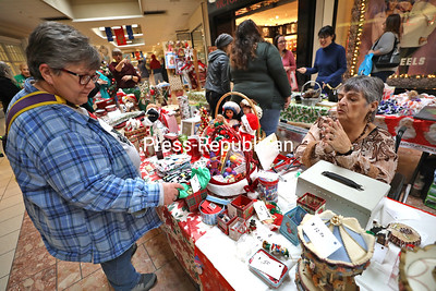 Holiday shopper Laura Burnell (left) browses the craft tables while volunteer Kathie McCorry helps her find the perfect gift at the Elmore SPCA Holiday Fundraiser in Champlain Centre Mall. All items were made from local crafters and donated to Elmore. All proceeds from the fundraiser will benefit the Elmore SPCA in Peru. KAYLA BREEN/ STAFF PHOTO