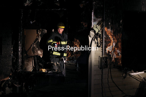 MIKE PITTS/ P-R PHOTO<br /> Investigators assess damage to the home of Becky and Joe Corral of 2 Marvin St. in Lyon Mountain Friday evening. The couple were awakened by their 1-1/2-yearold German shepherd, Spencer, and so made it out safely.