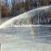 ROB FOUNTAIN/ STAFF PHOTO<br /> City of Plattsburgh Recreation Department employee Brent Martineau sprays down the ice rink at South Platt Park, creating a late afternoon rainbow Thursday. Martineau was preparing the rink for the South Side Sled & Skate festival, set for 5 to 8 p.m. Friday, Feb. 10. The free event, sponsored by the city, Breakfast Kiwanis Club and Reality Check, will feature night-time sledding and skating, music and food. It's part of the Snowball Celebration of Winter in the North Country.