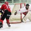 ROB FOUNTAIN/ STAFF PHOTO<br /> Beekmantown's Kaden Kowalowski (18) tries to maneuver the puck by Saranac goalie Konnor Shea (31) Wednesday during CVAC boys hockey at the AC-North Ice Rink in Plattsburgh.
