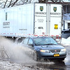 ROB FOUNTAIN/ STAFF PHOTO<br /> Cars and trucks travel on Boynton Avenue in the City of Plattsburgh, passing through wide, deep puddles and kicking up a deluge of water Wednesday. The previous 24 hours produced snow, sleet, freezing rain and milder temperatures that soaked the North Country. The forecast for Wednesday night was for temperatures in the teens, however, meaning more ice on the way.