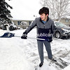 ROB FOUNTAIN/ STAFF PHOTO<br /> Ryan Beebie helps clear snow from a neighbor's driveway Monday in Plattsburgh. Sunday's snowstorm brought travel pretty much to a halt Sunday and caused many cancellations, including most schools, Monday.