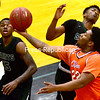 ROB FOUNTAIN/ STAFF PHOTO<br /> Clinton's Rayquan Brandford (22) plows through North Country defenders Donte Crumpler (15) and Sidney Alcena (23) for a layup during a men's basketball game Wednesday.