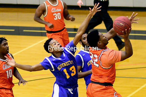 ROB FOUNTAIN/STAFF PHOTO 1-11-2017<br /> Clinton Community's Rayquan Branford (22) drives to the hoop with Schenectady's Sanuel Fraser (13) trying to block Tuesday during men's basketball in Plattsburgh.
