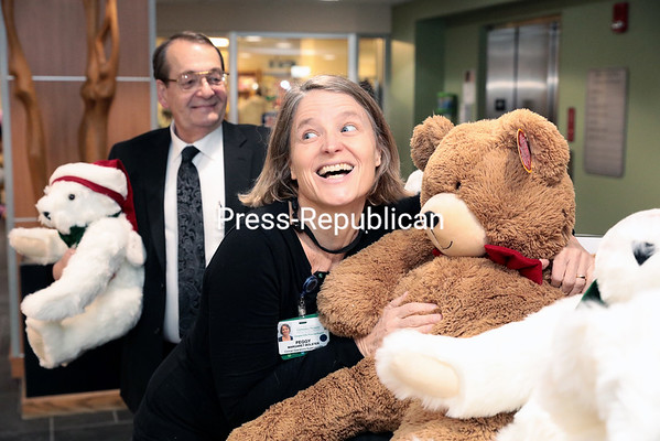 GABE DICKENS/P-R PHOTO 1-9-2017<br /> University of Vermont Health Network, Champlain Valley Physicians Hospital employee Peggy Bolster, Child and Adolescent Mental Health Unit Clinical Operations supervisor and resident nurse (center), carts off about a dozen teddy bears, manufactured by Vermont Teddy Bear Company and donated by George Rock (left) on behalf of the Press-Republican, in the hospital's lobby Thursday afternoon. The bears will be given to patients of the Mental Health Unit upon discharge.