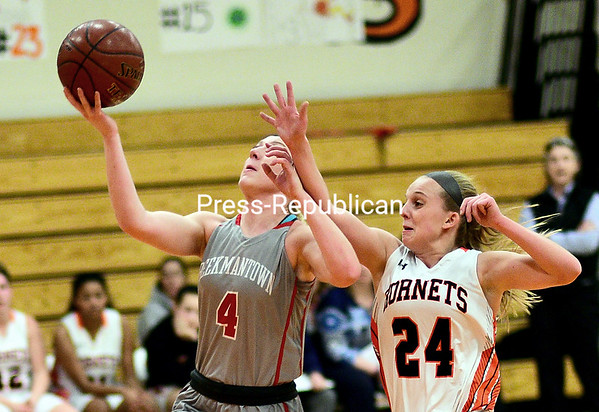 ROB FOUNTAIN/STAFF PHOTO 1-20-2017<br /> Beekmantown's Jordanne Manney (4) goes in for a layup with Plattsburgh's Shay Frady (24) trying to slow her down Wednesday during CVAC girl's basketball in Plattsburgh.