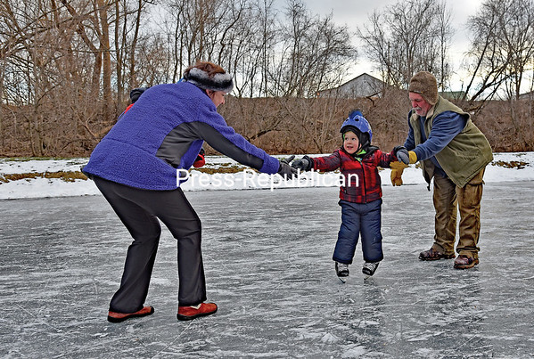 JOANNE KENNEDY/P-R PHOTO 1-8-2017<br /> Four-year-old Beckett Nicholls from Vermont tries his hand at ice skating for the first time as he reaches between his grandmother and grandfather, Cathy and Butch Santor from Plattsburgh, at the Little Ausable River Park in Peru. Beckett's 21-month-old brother Everett, who was not as keen on the outdoor sport, is tucked safely in his grandmother's arms.