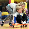 GABE DICKENS/P-R PHOTO 1-9-2017<br /> Jeannette Heins of Plattsburgh pushes her son, Noah, 5, on a scooter board, while her 4-year-old daughter, Emmy, gives chase during Family Fun Night at the Plattsburgh City Recreation Center. The event takes place from 6 to 8 p.m. every Saturday evening at a cost of $5 per family and includes basketball, a bounce house, rope climb and more.