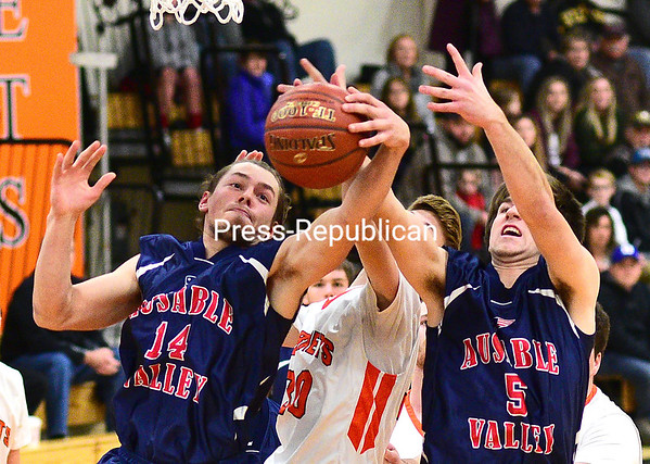 ROB FOUNTAIN/STAFF PHOTO 1-8-2017<br /> AuSable Valley's Kobe Parrow (14) and Dalton McDonald (5) take a rebound away from Plattsburgh High's Andrew Follmer (30) during a Champlain Valley Athletic Conference boys basketball game Wednesday in Plattsburgh.