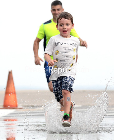 Benjamin Larche, 5, of Plattsburgh, sprints through the remnants of Thursday's rain with his father, Travis, in hot pursuit at the City Beach. Travis and his wife, Jamie, had planned to participate in the Mayor's Cup 5K, but it was cancelled with the threat of more storms brewing in the area.<br /> GABE DICKENS/P-R PHOTO