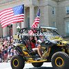 Karyssa Pryce and Ryan Cogswell wave from their Body Art Tattoo Can-Am all-terrain vehicle while taking part in the City of Plattsburgh's Fourth of July parade.<br /> KAYLA BREEN/STAFF PHOTO