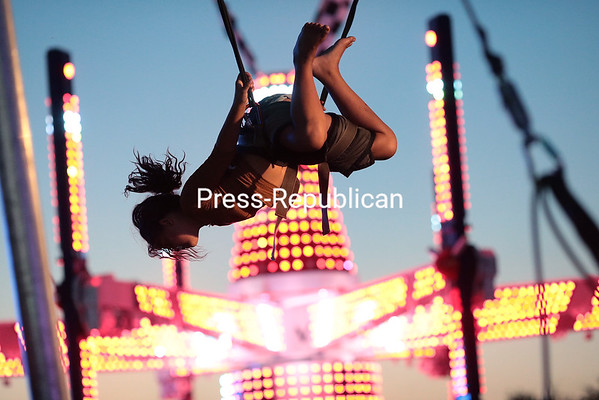 Jazmyne Chandler, 10, of Kingsport, Tenn., flips around while connected to a bungee harness with a trampoline beneath her at the Clinton County Fair in Morrisonville Thursday evening. Jazmyne accompanied her father, Barrington, of Cape Coral, Fla., to the area on vacation. Barrington manages a fleet of trucks that transports the rides to various fairs throughout the country.<br /> GABE DICKENS/ P-R PHOTO