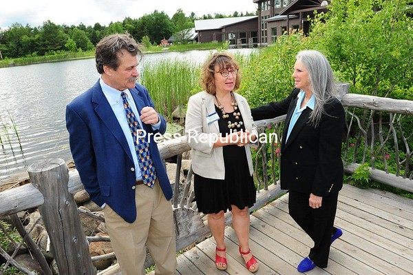 The Wild Center Executive Director Stephanie Ratcliffe (center), Susan Lawson and Tom Lawson of the Adirondack Club talk over the club's gift of 34 acres. The oxbow in the Raquette River there is rich wildlife habitat and is where Wild Center canoe and stand-up paddleboard trips start their daily excursions during the summer.<br /> JACK LADUKE/P-R PHOTO