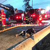 A frightened calf sits on the pavement after being carried from the burning barn by firefighters, its back turned to the commotion of firefighting. It was quickly brought it to a field to join other bovines saved from the flames.<br /> KAYLA BREEN STAFF PHOTO