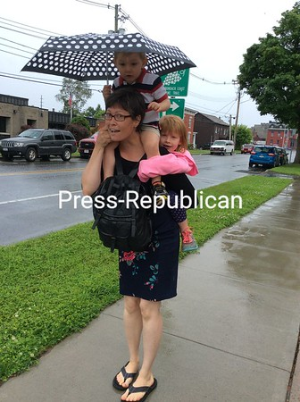 "SUZANNE MOORE/ P-R PHOTO<br /> Jamie Slominski keeps both David, 2, and Celestra, 5, dry as she walks along Margaret Street in Thursday's rain. Her children were getting a bit heavy, she admitted, ""but we're almost home."" David and Celestra were enjoying the ride."