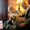 BEN ROWE/ STAFF PHOTO<br /> With another steady snowfall outside, Pat (left) and Ron Martin enjoy a cozy cuddle with their yellow labrador, Murphy, in their Plattsburgh home. Murphy was brought back safely to the Martins on March 23, 10 days after going missing during a massive winter storm.