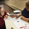 SUZANNE MOORE/ STAFF PHOTO<br /> Sandy Reese of Morrisonville (left) pays close attention to instruction from artist Lorrie Mandigo during the recent Enhanced Adult Coloring class at Strand Centre for the Arts in Plattsburgh. A little know-how about shading with colored pencils or watercolor markers adds vibrancy and dimension to a the artist said. The Strand offers a broad spectrum of classes, including clay, fiber arts, framing, photography, theater and dance. Mandigo has her own studio, too; Lorrie Mandigo Art Studio & Gallery is located at 30 Broad St., Plattsburgh.