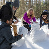 GABE DICKENS/ P-R PHOTO<br /> SUNY Plattsburgh students Neel Adalja (from left), a native of India; Alex Rabia of Algeria; and Adhamjon Makhamadjanov from Uzbekistan join their English as a Second Language teacher, Holly Carey, in creating an impromptu snowman during an outing to the New Land Trust in Saranac on a recent afternoon. With rental snowshoes provided by the college, the students trekked throughout much of the trust's 287 acres, with Cadyville native Conor Carrigan acting as their guide.