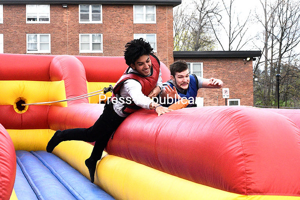 KAYLA BREEN/ STAFF PHOTO<br /> Matteo Chavez (left) and Tyler Ellis both reach out to grab the ball first during an inflatable challenge at SUNY Plattsburgh's Spring Carnival. Students were invited to take a break from studying to enjoy live music, food and activities such as slacklining and tie-dying.