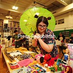 JACK LADUKE/ P-R PHOTOS Tamara Wilson holds a colorful umbrella as she looks over her handmade doll clothing, which she was selling at the Malone Comic Con on Saturday. The event was moved t ...