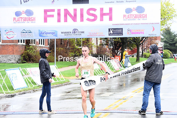 KAYLA BREEN/ STAFF PHOTO<br /> Carrie Pomainville smiles at the finish line before becoming the first female to finish Sunday during the eighthannual Plattsburgh Half Marathon. Pomainville finished the race in one hour, 31 minutes and 44 seconds. She placed 24th overall.