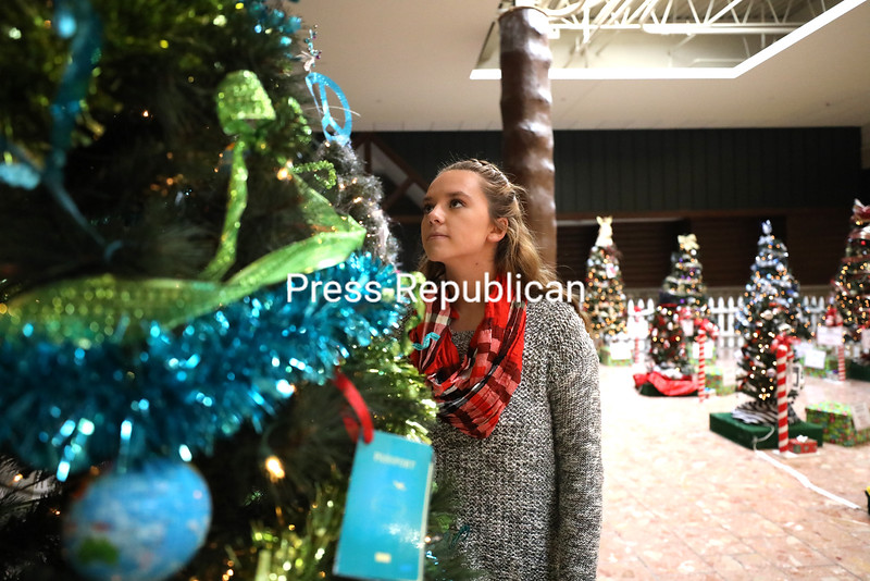 Shayna White admires the passport and globe ornaments adorning the Primelink-decorated Christmas tree at the Festival of Trees inside Champlain Centre mall in Plattsburgh. Dozens of local businesses and organizations decorated trees for the event, which raises money for the ARC Foundation. The trees are raffled off, with winners announced at 6 p.m. Saturday, Dec. 2.<br /> KAYLA BREEN/ STAFF PHOTO