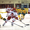 Plattsburgh State's Ashley Songin (12) carries the puck through the neutral zone as Oswego's Kate Randazzo (21) looks to poke check the puck away during a Northeast Women's Hockey League game Saturday at Stafford Ice Arena.<br /> KAYLA BREEN/ STAFF PHOTO