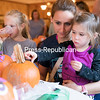 Three-year-old Alexandra Roberts, held by her mother, Rachelle, decorates a pumpkin with adhesive foam eyes as her sister, Natalie, 5, sips apple cider during the recent Kids Night at the Elks Lodge in Plattsburgh. The event featured pumpkin decorating, food, games and a petting zoo with animals from the Plattsburgh 4-H Club.<br /> GABE DICKENS/ P-R PHOTO