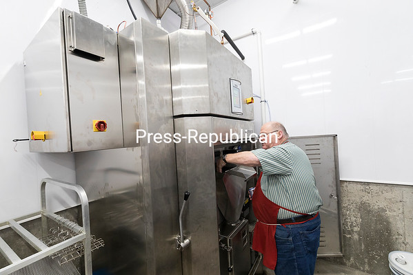Adrien Dutil shows visitors some of the equipment at D& D Meats, including an $80,000 Kerres smokehouse imported from Germany, an $18,000 emulsifier for making hot dogs and a vacuum packer for packing meat. GABE DICKENS/ P-R PHOTO