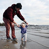 Gregg Castelluccia helps his daughter, 10-month-old Mary Mannix, walk along the beach at Point au Roche State Park in Beekmantown during an unusually warm autumn evening. Castelluccia and his wife, Katelynn Mannix, are Plattsburgh natives who moved to Fairfield, Conn., in 2011, and were back in town for a friend's baby shower.<br /> GABE DICKENS/ P-R PHOTO