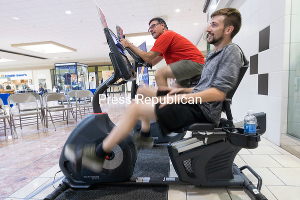 Jack Helfgott (left), president-elect of the Plattsburgh Noontime Rotary Club, and Joel Arnone, chairman of the membership committee for the Plattsburgh Sunrise Rotary Club, ride stationary bikes during the two-day Rotary World Polio Day Fundraiser at Champlain Centre mall in Plattsburgh Sunday afternoon. Rotary members, volunteers and passers-by rode the bikes in 15-minute intervals to raise polio awareness and money for Rotary International's PolioPlus Foundation, which was created 32 years ago to help rid the world of the dreaded disease. The campaign, which is a part of the Global Polio Eradication initiative, involves the World Health Organization, U.S. Centers for Disease Control and Prevention, United Nations Children's Fund and the Bill & Melinda Gates Foundation, and has reduced polio cases 99.9 percent worldwide. GABE DICKENS/ P-R PHOTO