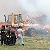 A front-end loader is used to smother burning tires with dirt after fire spread from the destroyed maintenance building.<br /> GABE DICKENS/ P-R PHOTO