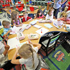 Students in Jillian Devins's kindergarten class sit around a semi-circle desk to decorate cards with hearts, rainbows and happy messages to accompany Hurricane Harvey care packages for the children of Refugio Elementary School in Rufugio, Texas, and the Aransas School District in Rockport, Texas.<br /> KAYLA BREEN/ STAFF PHOTO
