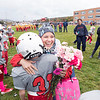 "April Wood, an officer with the Plattsburgh City Court system who is in treatment for Stage 2 breast cancer, embraces Edward Sweenor of the Adirondack Football League's junior varsity Beekmantown Eagles during a surprise ceremony held for Wood. Each player, clad in pink socks, eye makeup and ribbon stickers on their helmets, presented her with a pink carnation prior to a recent game against the Saranac Chiefs, which April's 9-year-old daughter, Rowan, plays for, at Saranac Central School. April and her husband, Adam Wood, a Plattsburgh City Police officer, moved to Saranac two years ago from Beekmantown, where Rowan had played flag football with many of the same kids. The players also presented April with a pink football signed by the entire team, a gift certificate and a check for $250, which was raised through the Run for the Tatas 5K Poker Run last month in Plattsburgh. April, diagnosed with cancer on June 23, is halfway through her chemotherapy treatment. ""I fully expect to fight the fight and come out a survivor on the other end,"" she said.<br /> GABE DICKENS/ P-R PHOTO"