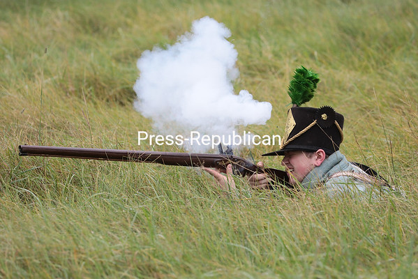An American soldier returns fire during a reenactment battle in the U.S. Oval field Saturday morning as part of the Battle of Plattsburgh Commemoration. The U.S. Oval will host activities for all ages today from 10 a.m. to 3 p.m. as part of the commemoration festivities.<br /> GABE DICKENS/ P-R PHOTO