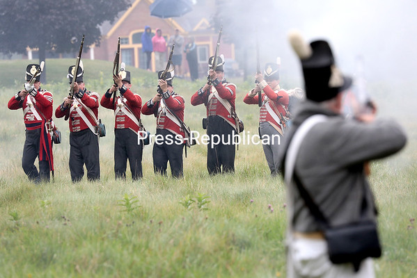 British troops raise their guns to fire on retreating American forces during a reenactment for the Battle of Plattsburgh Commemoration Saturday morning near the U.S. Oval. From 11 a.m. to noon today, reenactors will act out the American defense of Bridge Street from British forces in Downtown Plattsburgh.<br /> GABE DICKENS/ P-R PHOTO