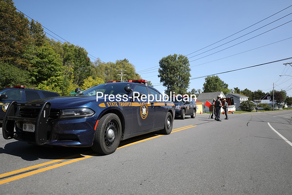 """State Police Sgt. Richard White and Troopers Michael Harmon and Troy Nelson direct traffic at a road block at the intersection of Route 374 and Eggleston Drive in Dannemora, diverting vehicles away from filming of the Showtime production """"Escape at Dannemora."""" KAYLA BREEN/ STAFF PHOTO"""