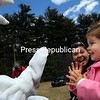 While Maggie Pulsifer was not sure what to make of the Easter Bunny, her mother, Sasha, seemed to be enjoying the moment. The Pulsifers were among families who visited the Noble Terrace in Elizabethtown Saturday for an Easter egg hunt sponsored by the Elizabethtown/Lewis Youth Commission. A swarm of youngsters scoured the field and woodland borders of the garden to find 3,500 Easter eggs, each which contained a treat or prize. The event also featured cotton candy, a bounce house and three prize Easter baskets provided by Denton's Bare Necessities. Each participant also received a certificate good for a kid's meal at Perkins and a free play of a game at Fun City.<br /> ALVIN REINER/ P-R photo