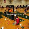 Youngsters flock to the Easter-egg-filled floor of North Country Community College to gather up as many colorful eggs as possible. The school's Athletic Department spent a week filling and laying out 3,000 eggs.<br /> JACK LADUKE/ P-R photo
