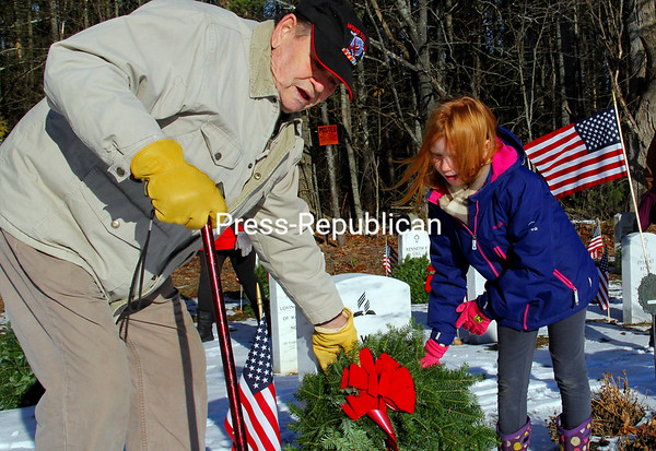 KAYLA BREEN/STAFF PHOTO  Art Pulsifer, who served in occupied Berlin after WWII, and his great-grand-daughter, Erin, both of Wadhams, were among those who placed wreaths on the tombstones at the Essex County Veterans Cemetery for the recent Veterans Cemetery Committee and the Elizabethtown American Legion event patterned after the National Wreaths-Across-America event that takes place annually in early December and is observed at the Arlington National Cemetery and at many other military cemeteries across the nation. Though they have no relatives interred there, Pulisfer paid his respects to several friends.