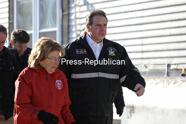 Gov. Andrew Cuomo and State Sen. Betty Little walk between mobile homes as they make their way to the berm that failed to hold floodwaters back at Underwood Estates in Plattsburgh. They and other elected officials toured of the mobile home park to see first-hand the damage that was caused by ice jams on the Saranac River. Cuomo promised state funds will be made available to repair or replace the homes.<br /> KAYLA BREEN/ STAFF PHOTO