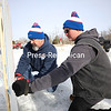 Rick Duquette (left) and Mike Layhee drill in Labatt Blue decorative signs along the barrier of the curling rink as they prepare for the 11th-annual Winterfest Celebration at American Legion Post 1619 in Morrisonville. The celebration kicks off today and continues into Sunday.<br /> KAYLA BREEN/ STAFF PHOTO