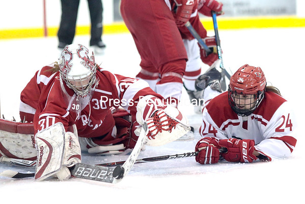 Plattsburgh State's Abby Brush swipes at a puck that had been poked aside by Cortland goaltender Rachael Farmer during Sunday's NEWHL game at Stafford Ice Arena. GABE DICKENS/ P-R PHOTO
